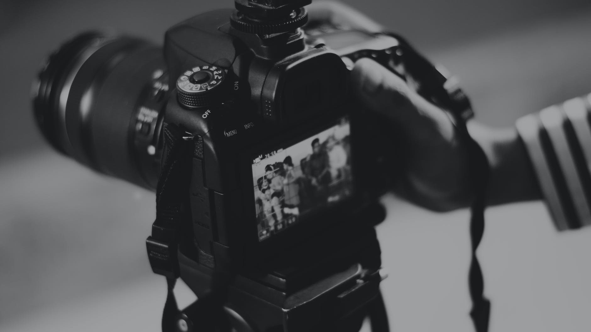 grayscale photography of person holding black dslr camera